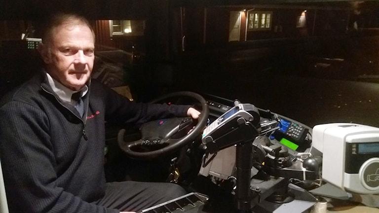 Weine Arwidsson sitter på förarsätet i en buss. Utanför bussen är det mörkt.