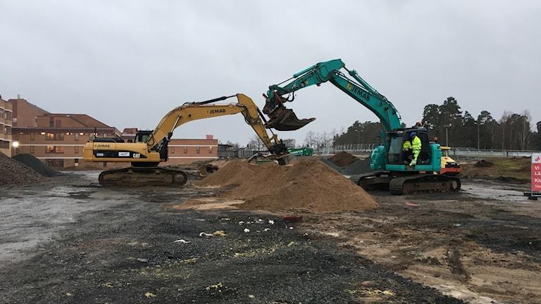 Två grävmaskiner gräver i en jordhög.