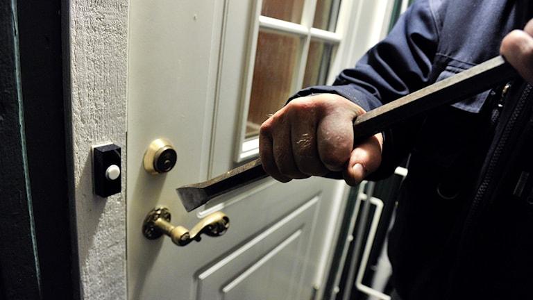 En man försöker bryta upp en ytterdörr med en kofot.