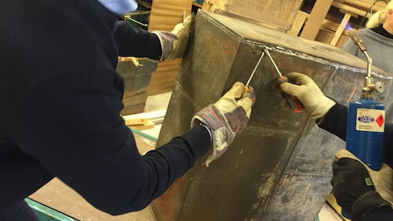 Händer med skyddshandskar öppnar plåtlådan med olika verktyg.