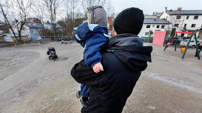 En förälder håller i sitt barn vid en lekplats