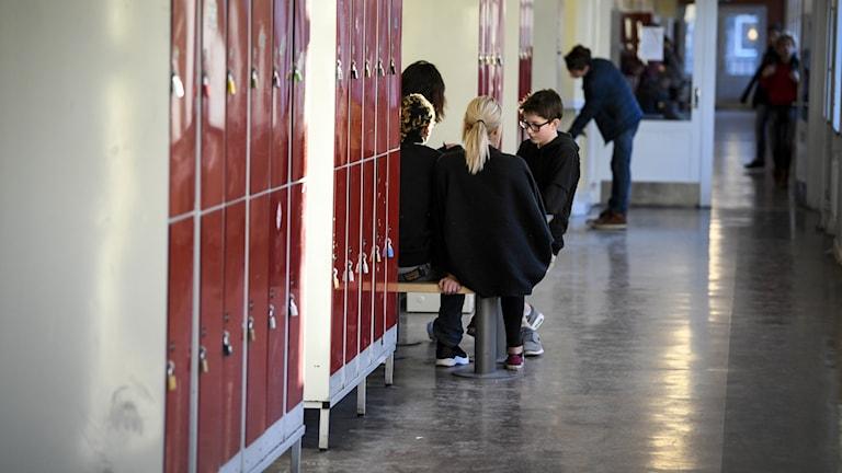 Röda skåp och sittande elever i en skolkorridor med grått golv.