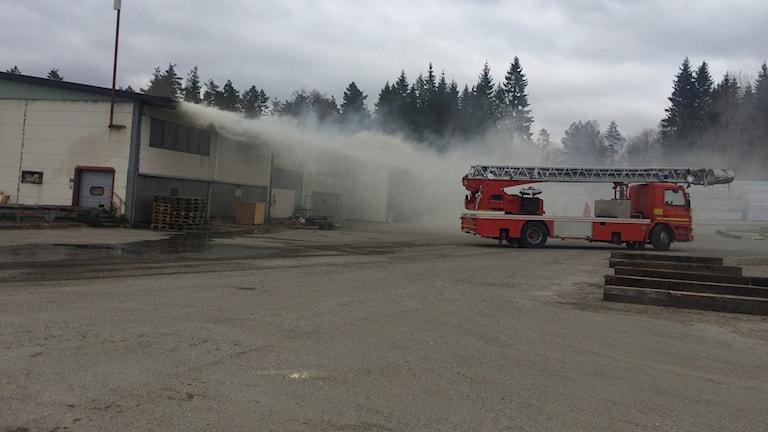 Rök kommer från en vit byggnad. En brandbil står bredvid.