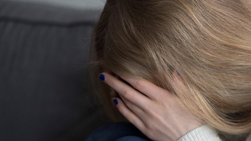 En flicka håller för sitt ansikte.