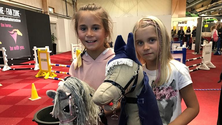 Två flickor med varsin käpphäst.