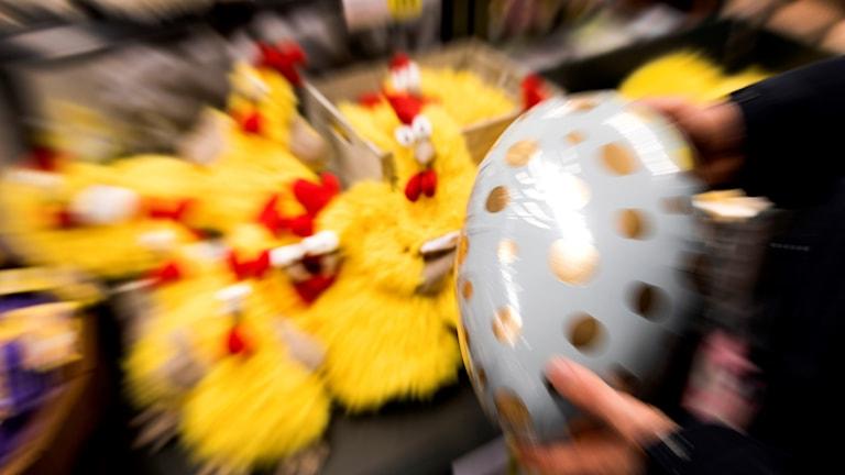 En person håller i ett påskägg vid en hylla med gula kycklingar.
