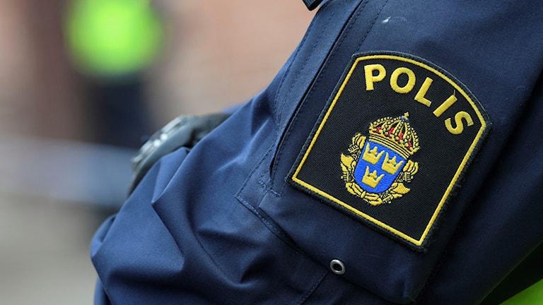 Närbild på en polislogga på en blå jackärm.