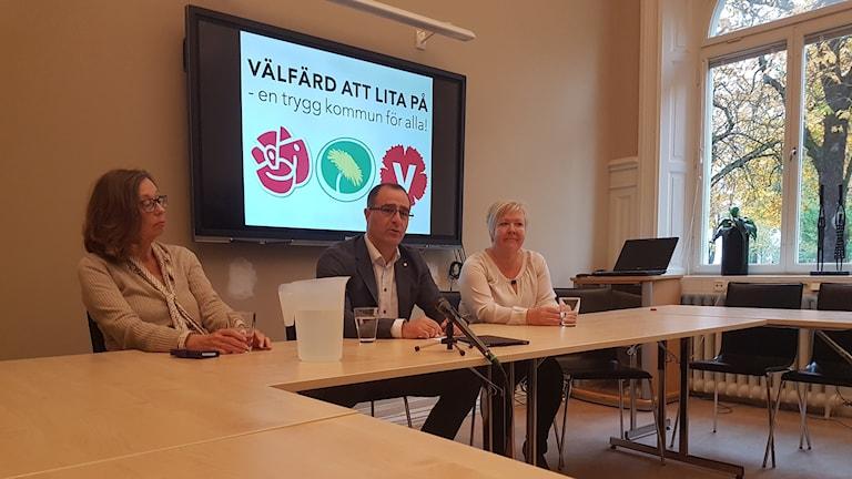 Tre personer sitter vid ett bord under en presskonferens.