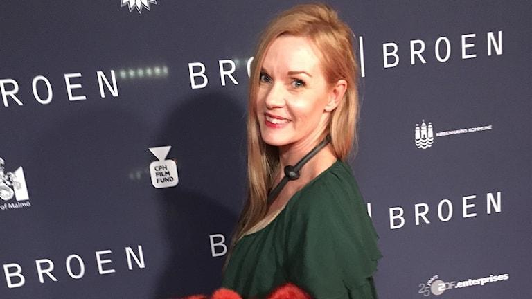 """Pia Johansson framför en vägg med texten """"Broen""""."""
