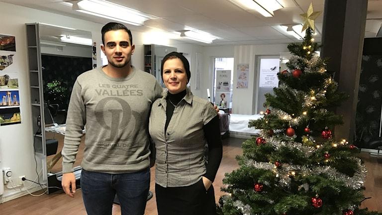 Två personer står bredvid en julgran inne i en frisersalong