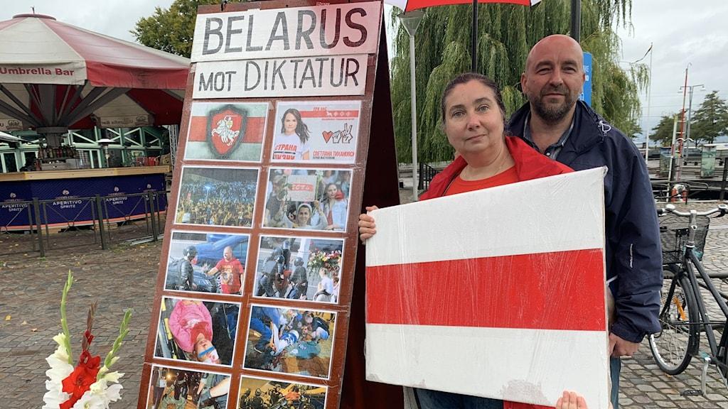 Två personer står med plakat där det står Belarus mot Diktatur