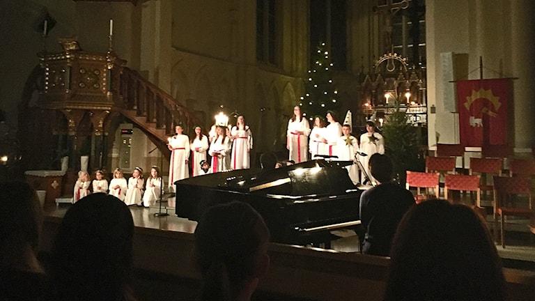 Lucia och tärnor framför kyrkoaltaret.