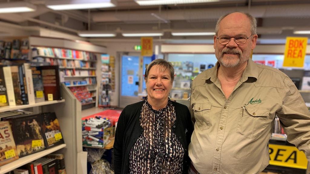 Ett par står i bokhandeln.