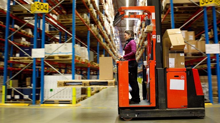 En kvinna kör en truck bland höga hyllor i en lagerlokal.