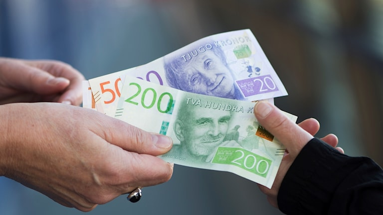Två händer byter sedlar.