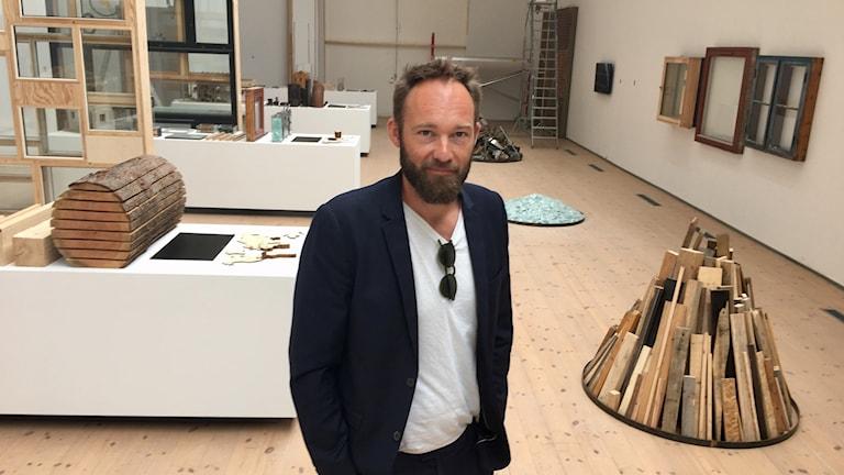 Anders Lendeger står i ett rum med olika konstverk.