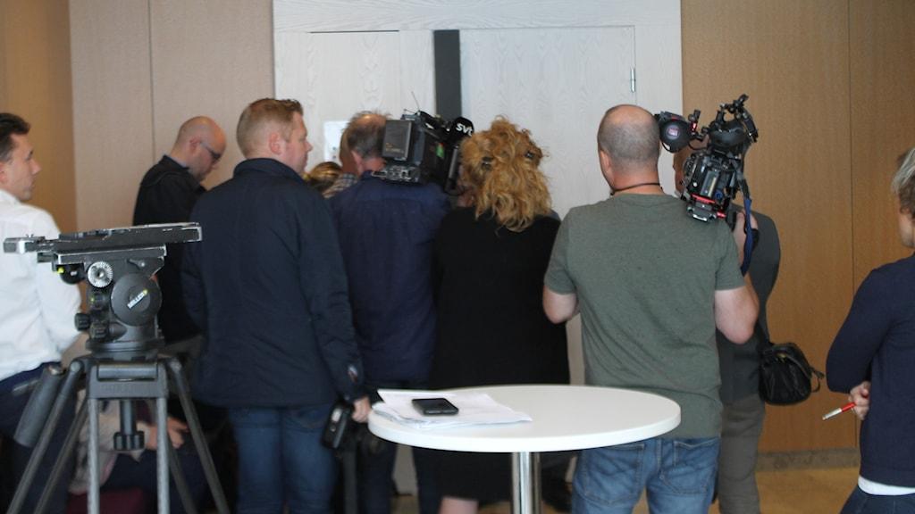 Ett tiotal journalister med kameror utanför rättssalen.