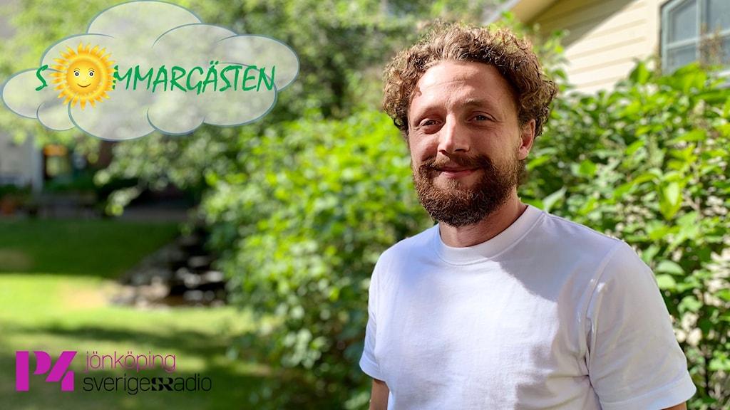En man i vit t-shirt står i en grönskande trädgård med sol i ansiktet