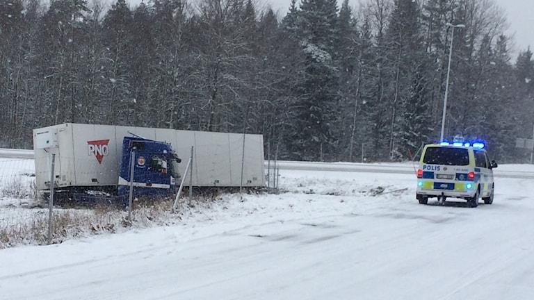 En lastbil står vid sidan av en snöig väg. En polisbil står på vägen.