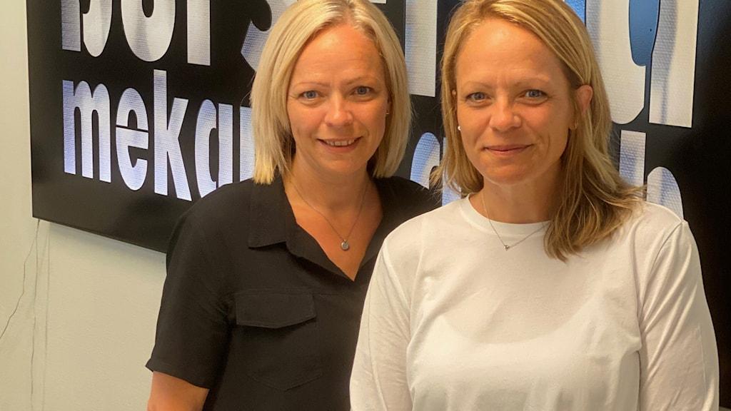 Två kvinnor framför en företagsskylt