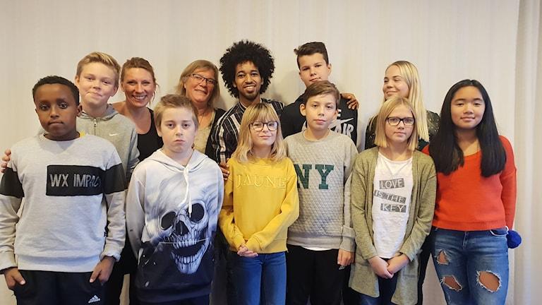 Mousa Mousa står i mitten med flera skolbarn runt sig.