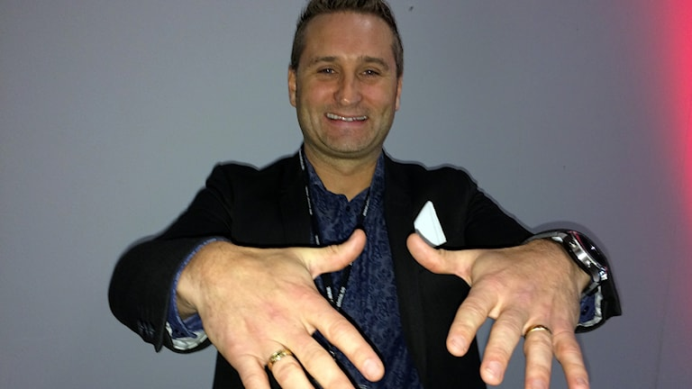 Fredrik Hoel håller fram sina händer mot kameran och ler.