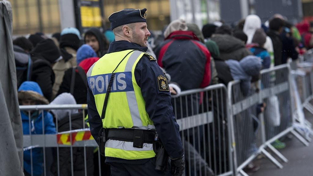Flyktingar står i kö för att komma in i Sverige. Övervakas av polis