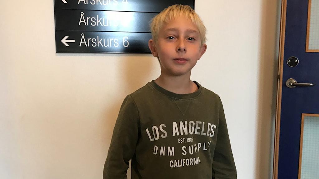 Alex nio år står framför en vägg i sin skola.