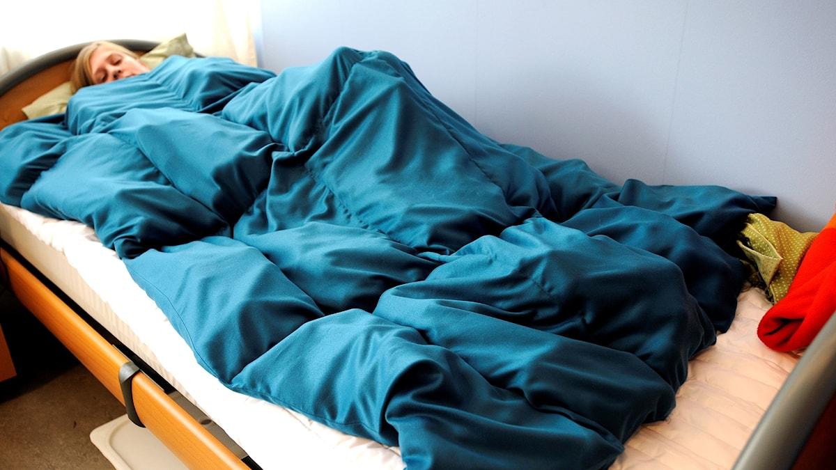 En kvinna i sängen med ett tyngdtäcke.