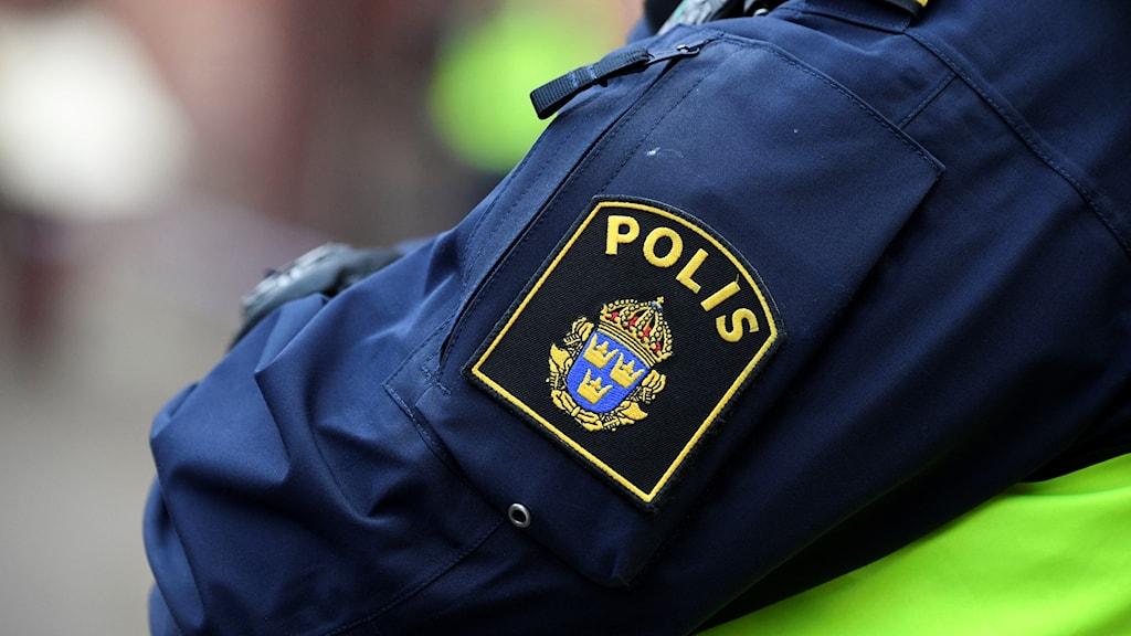 Närbild på ett polismärke på en jackärm.