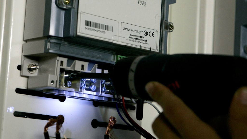 En elektriker använder en borrmaskin vid ett elskåp.