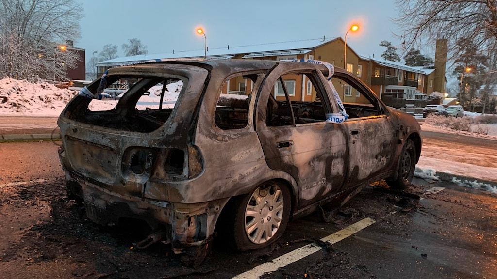 En utbränd bil på en parkering.