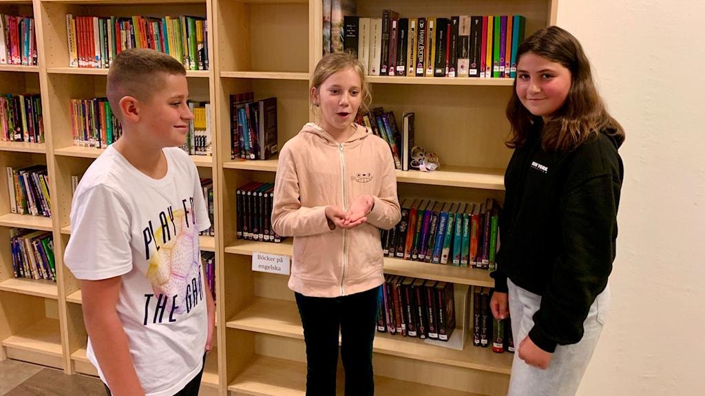Tre mellanstadieelever pratar vid en bokhylla.