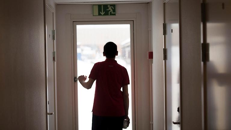 Asylsökande ser ut genom ett fönster på ett flyktingboende.