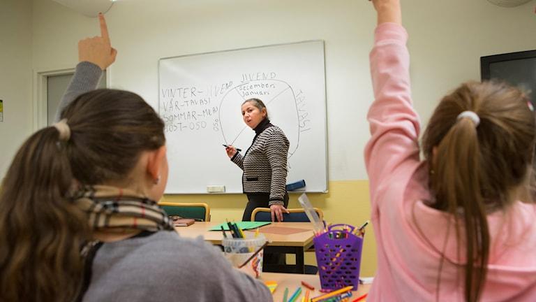 Två flickor räcker upp handen i ett klassrum. En lärare står vid tavlan.