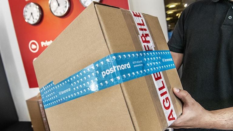 Man håller i kartongpaket med blått Postnord-band omkring.