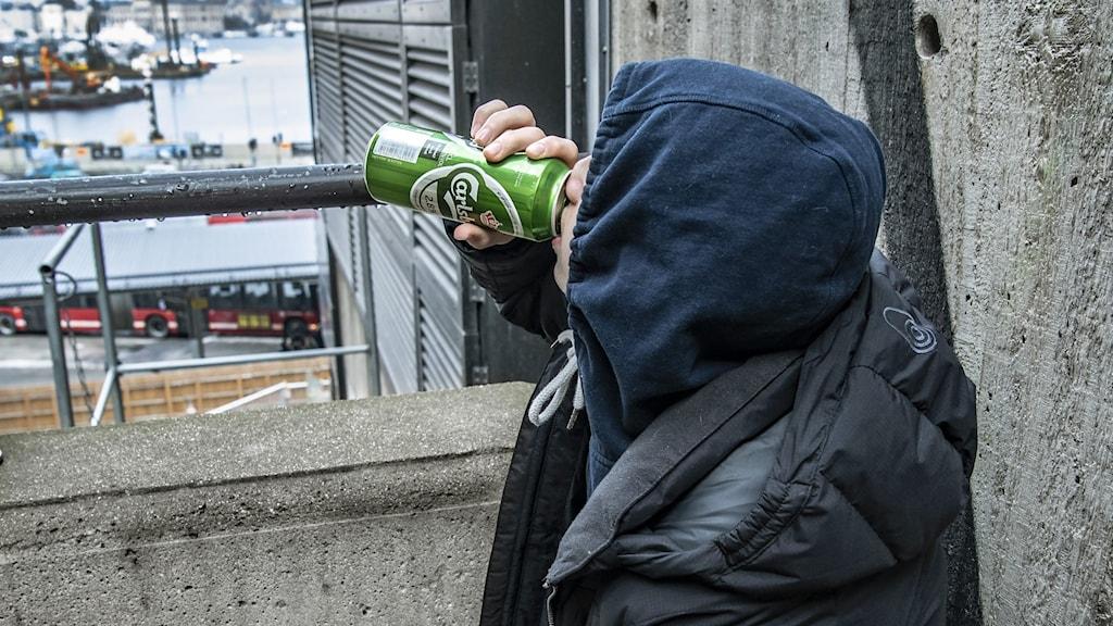 En ung man i luvtröja dricker en burk öl
