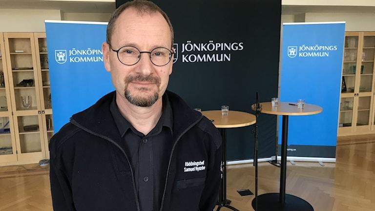 En man står framför en roll-up med texten Jönköpings kommun.