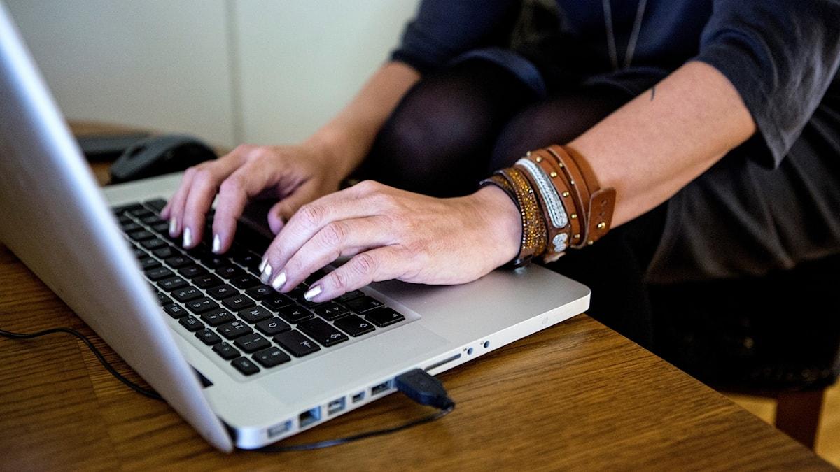 Närbild på en kvinnas händer på tangentbordet på en laptop.