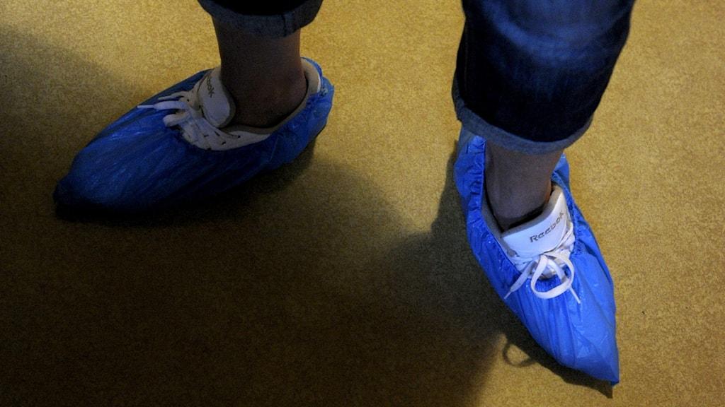 Person från hemtjänsten med blåa plasttossor på fötterna.