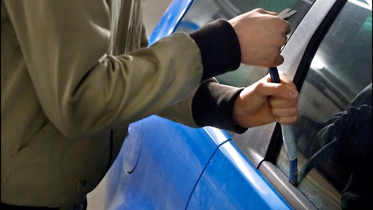 En person bryter sig in i en bil med hjälp av en kofot.
