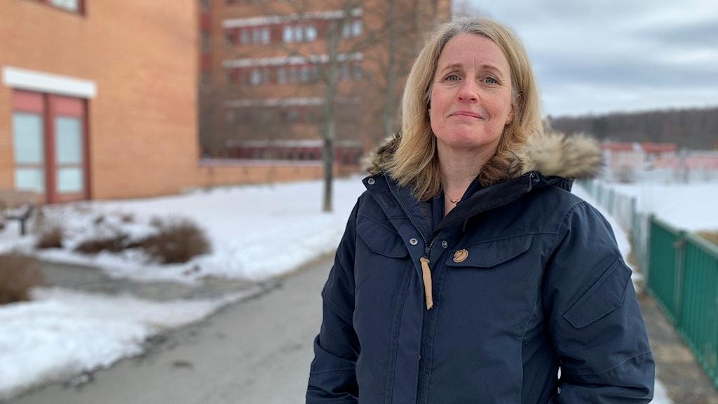 Barnläkaren Maria Ekelund står utanför en tegelbyggnad. Hon har en blå täckjacka på sig.