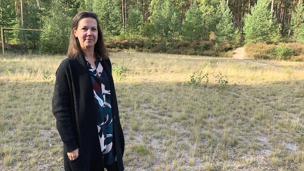 Handläggare Linda Lorant står på den just nu vildvuxna gräsplätt med granar i bakgrunden som ska bli det nya bostadsområdet.