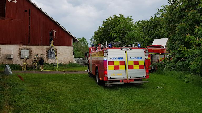 En brandbil står framför ladan som fattade eld efter att blixten slagit ner. Flera brandmän står omkring en stege och arbetar.