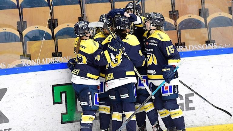 Glada hockeyspelare kramar om varandra.