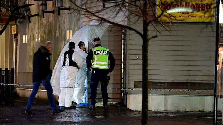 Poliser står vid en avspärrat byggnad.