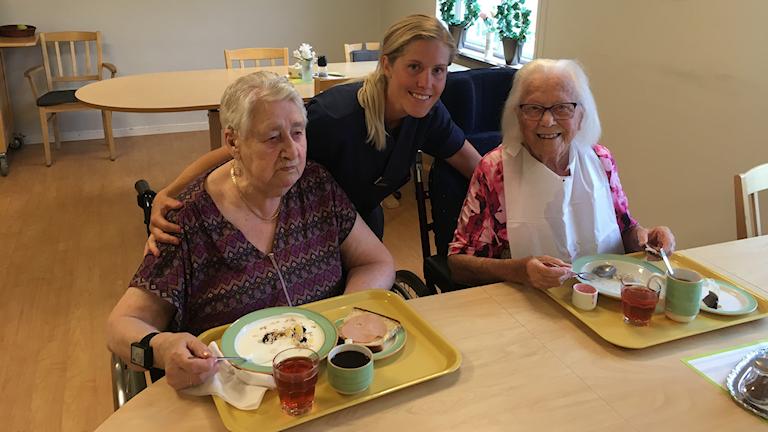 En ung kvinna i blå uniform står bakom två sittandes äldre kvinnor. På bordet framför står två frukosttallrikar.
