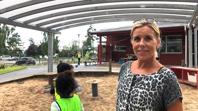 Kvinna på en förskola med sand och barn i bakgrunden.