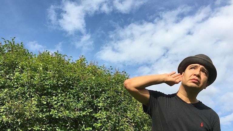 Johan Palm står och lyssnar efter ett ljud i himlen.
