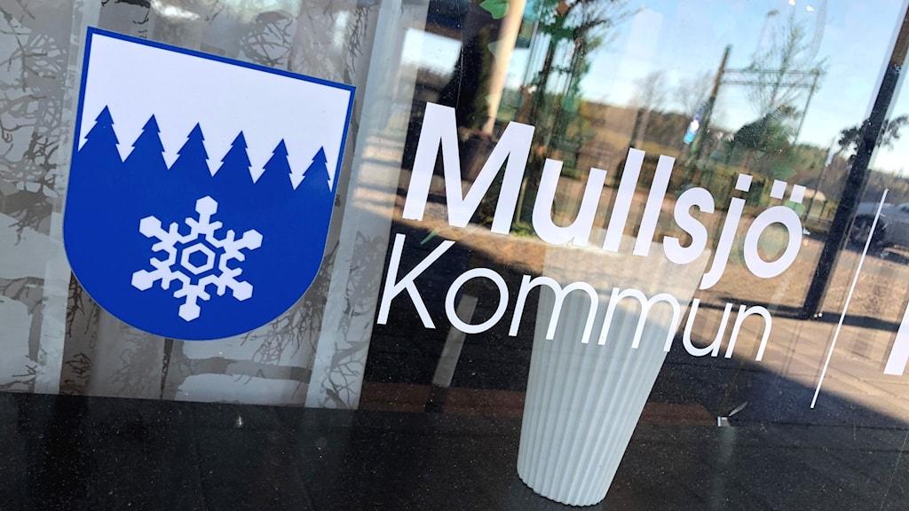 """En bild på fönstret in till Mullsjö kommuns kommunhus, där det står """"Mullsjö kommun"""" i vit text på glaset."""